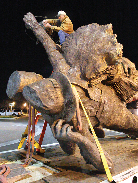 STATUE AT ROUNDABOUT3 (12-06-13)  Rowland Cheney runs electrical wiring through his ÒHarvest of ProgressÓ statue before it is raised over a platform at the center of the Sixth Street-Central Avenue roundabout late Dec. 5.  Glenn Moore/Tracy Press